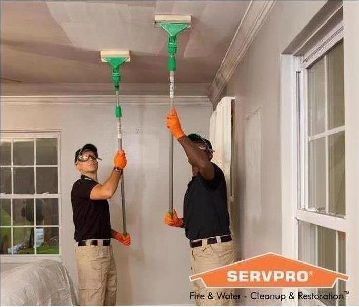 SERVPRO employees cleaning soot off of ceiling