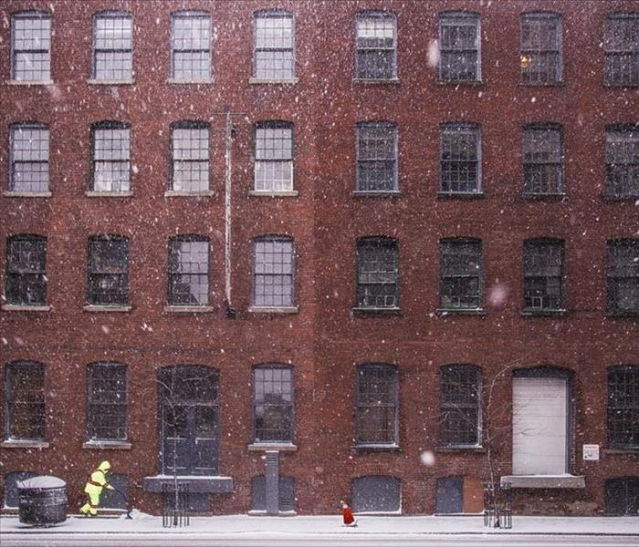 building with snow falling and man removing snow