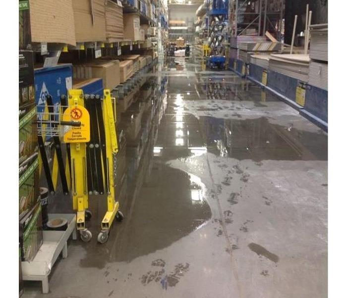 store floor with water damage and crew and equipment in background