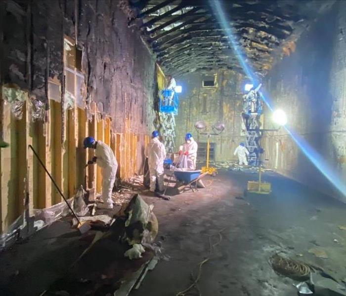 fire damaged interior of building with crew working